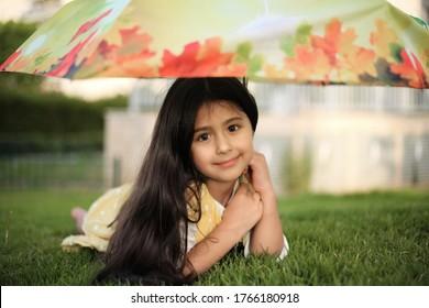 Porträt eines kleinen Mädchens mit Regenschirm. Mutterschaft, Kindergarten, Kindheit