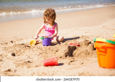 Portrait of a little girl using buckets and toy shovels to build a sand castle at the beach