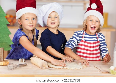 Portrait of little girl using cookie cutters on dough with sisters at kitchen counter