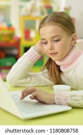 Portrait of little girl using laptop while sitting