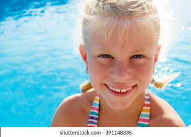 Portrait of a little girl vacationers beside swimming pool in a sunny summer day