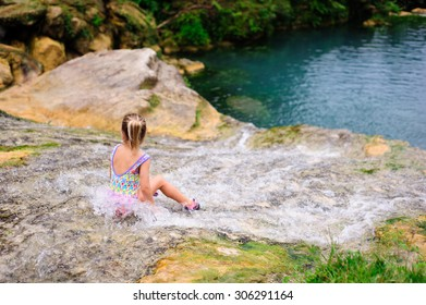 A portrait of a little girl wearing a colourful swimming suit sitting in the flowing water of Vanuatu cascades with her back turned to the camera