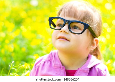 portrait of a little girl wearing glasses, outdoors