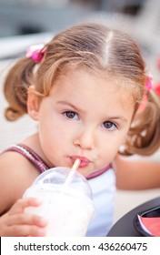 portrait of a little girl who drinks milk or milkshake