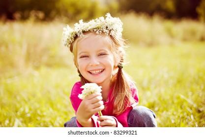 Portrait of a little girl in wreath of flowers