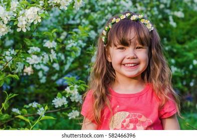 portrait of a little girl with a wreath on his head in the summer the lush Apple orchard