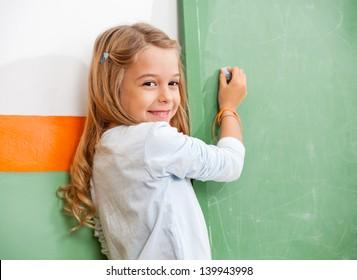 Portrait of little girl writing on green chalkboard in classroom