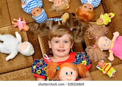 portrait of little girl(child, kid) with dolls on the carpet