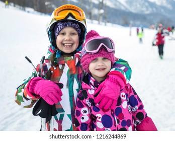 Portrait of little girls on alpine skiing skating on slope in ski resort