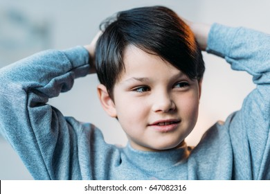 portrait of little happy boy smiling with hands on head at home