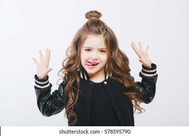 Portrait of little hipster girl in bomber jacket showing tongue. Posing. Curly modern hairstyle. Smiling. Studio