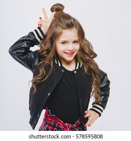 Portrait of little hipster girl in bomber jacket showing horns by hands. Posing. Curly modern hairstyle. Showing peace by fingers. Smiling. Studio