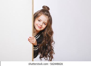 Portrait of little hipster girl looking out. Curly hairstyle. Copy-space