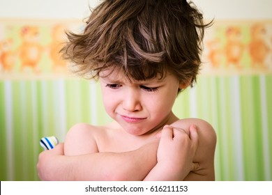 Portrait of little kid with angry upset face expression. Cute child making a sad face