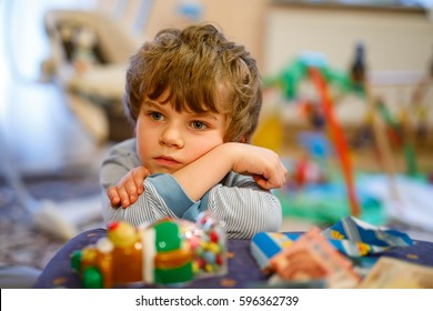 Portrait of little kid boy sad on birthday. child with lots of toys. Tired preschool boy