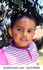 Portrait of a little kid at Holi festival. He is enjoying the festival.