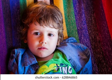 Portrait of little kid with upset face expression. Cute child making a sad face