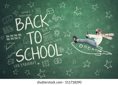 Portrait of little kid wearing helmet and scarf while driving rocket picture and doodles on the chalkboard