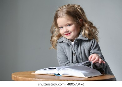 Portrait of little lady in coat with a book. Close up. Gray background
