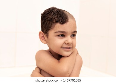 Portrait of a little middle eastern boy at the bathroom. 6-year-old pretty kid with half-cut hair at home. Father cut half of the son's hair off at the bathroom