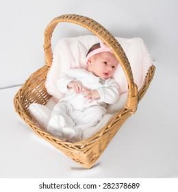 Portrait of little newborn baby lying in the basket