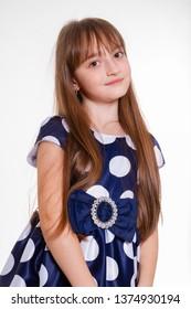 Portrait of a little positive schoolgirl in a polka dot dress