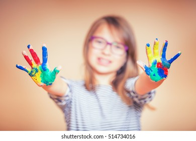 Portrait of a little pre-teen student girl showing painted hands.