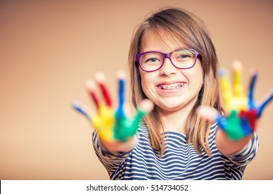 Portrait of a little pre-teen student girl showing painted hands. Girl with teeth braces and glasses.