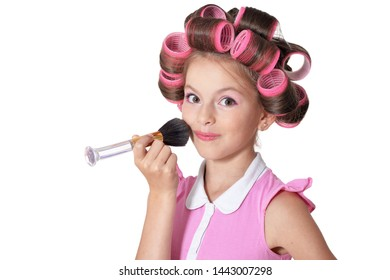 Portrait of little pretty girl with hair curlers with brush