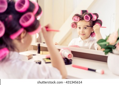 Portrait of little pretty laughing girl with pink hair curlers on her head , sitting on a chair in the dressing room and make yourself a makeover. He holds in his hand brush for applying makeup