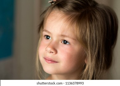 Portrait of little pretty young child girl with gray eyes and clip in scattered fine blond hair looking dreamily in distance on blurred sunny background. Beauty, dreams and innocence of childhood.