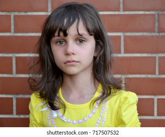 Portrait of the little sad girl against the background of a brick wall