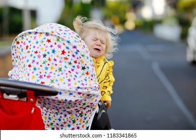 Portrait of little sad toddler girl sitting in stroller and going for a walk. Crying baby child does not want sitting in pram. Healthy daughter. Hysteric crisis of two years phase