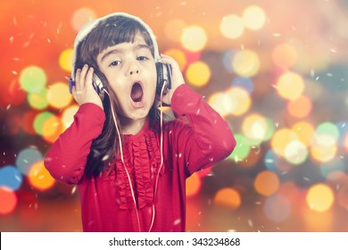 Portrait of a little Santa girl singing while listening to music. Defocused bokeh Christmas lights background. Cross processed image with shallow depth of field