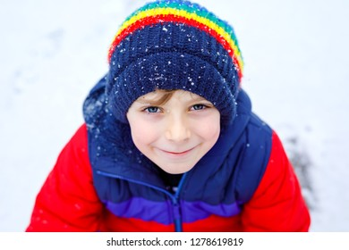 21fa5a27a65 Portrait of little school kid boy in colorful clothes playing outdoors  during snowfall. Active leisure