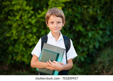 Portrait Little schoolboy with backpack and books. Outdoors.
