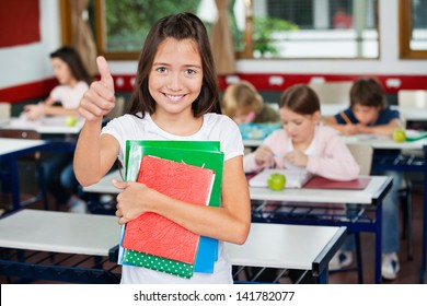 Portrait of little schoolgirl gesturing thumbs up while holding books with classmates studying in background