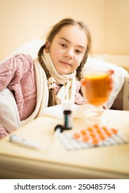 Portrait of little sick girl lying in bed taking cup of tea with lemon