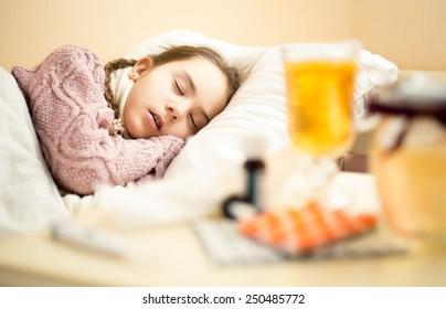 Portrait of little sick girl in sweater sleeping in bed