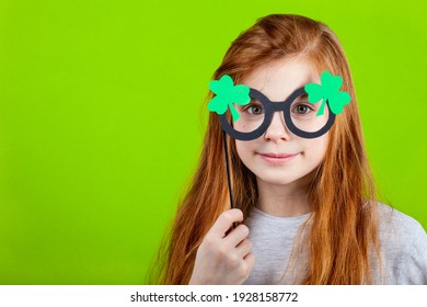 Portrait of little smiling caucasian red-haired girl in mask of leprechaun shamrock clover glasses for irish St. Patrick's Day on green studio background. Copyspace.