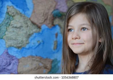 portrait of a little smiling girl against map background