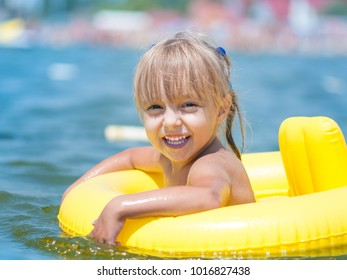 Portrait of little smiling girl with inflatable rubber circle in the sea in sunny day. Summer vacations concept.
