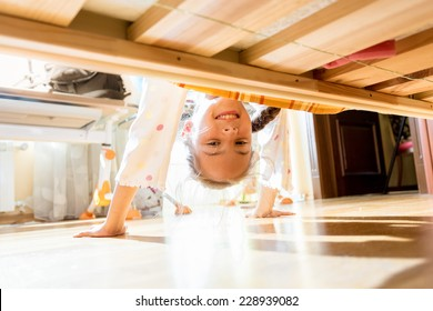 Portrait of little smiling girl looking under bed