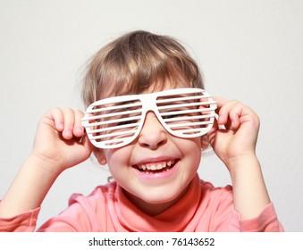 Portrait of little smiling girl, she try on white glasses-shutters