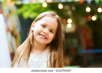 portrait of the little smiling girl in summer day. children's holiday of a birthday Outdoor.
