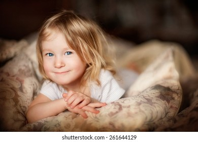 portrait of a little smiling girl with tousled blond hair lying on a bed