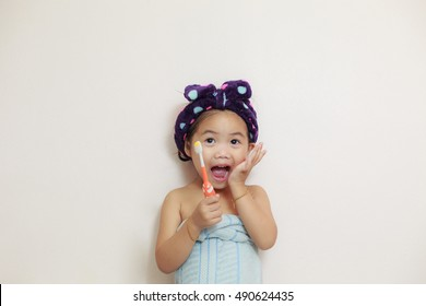 portrait of little smiling happy caucasian girl brushing her teeth standing indoors