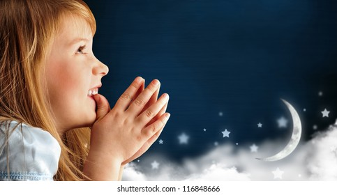 Portrait of little smiling praying girl in blue dress against dark fairy sky background with moon and stars. Lots of copyspace