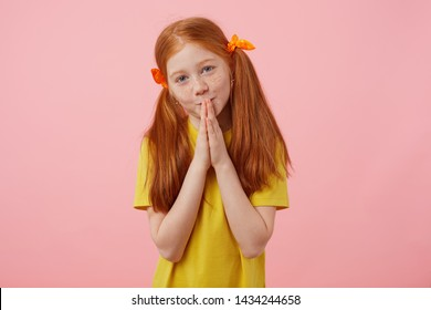 Portrait little sorry freckles red-haired girl with two tails, looks into the camera and cupped hands together, preyer gesture, wears in yellow t-shirt, stands over pink background.