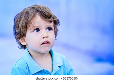 Portrait of a little toddler boy kid looking up with serious face expression on blue background